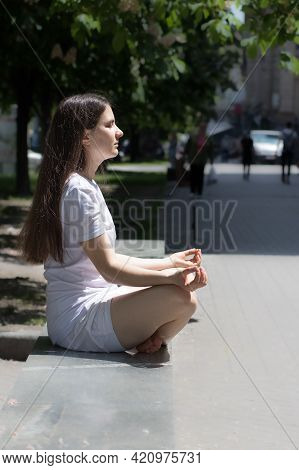Beautiful Brunette Woman In White Clothes Meditates On The Street In The City. Yoga And Meditation,