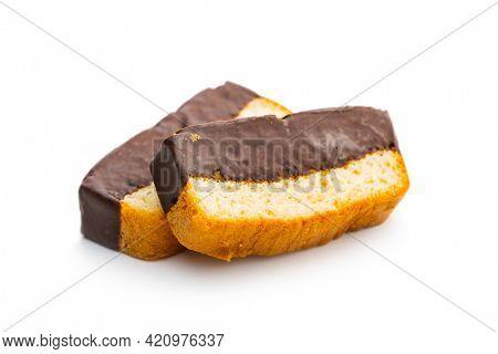 Sliced sponge dessert. Sweet sponge cake with chocolate isolated on white table.