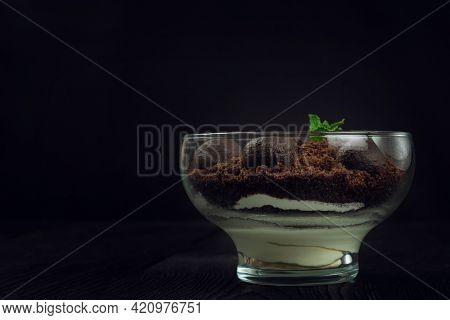 Chocolate dessert of cookies with pieces of chocolate and mint on a dark wooden background with copyspace, food and drink concept