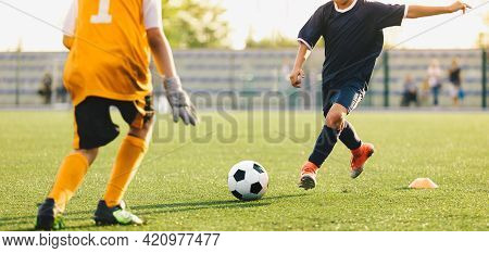 Kids Playing Football. Soccer Forward Player Kicking Ball Towards Young Goalkeeper. Soccer Duel On S