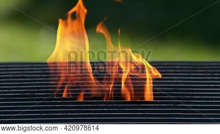 Empty grill grid with fire. Outdoor barbecue preparation, space for product placement.