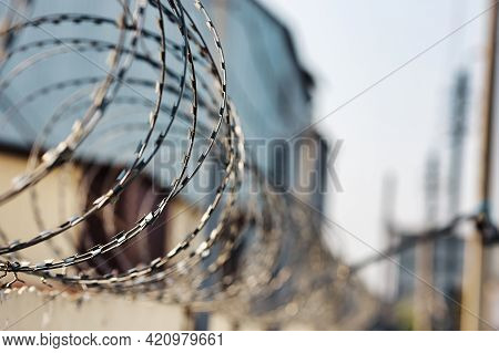 Spirals Of Barbed Wire On A Concrete Fence. A Symbol Of Incarceration And Lack Of Freedom. Punishmen