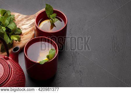 Herbal tea with mint and lemon. Tea cup and teapot on stone table. With copy space