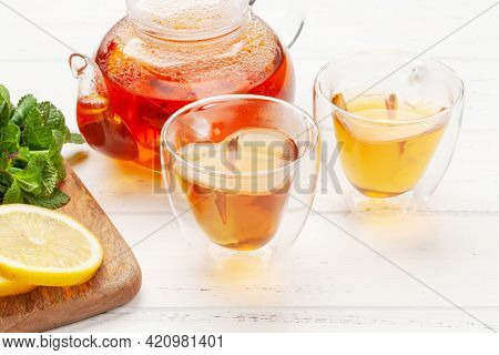 Herbal tea with mint and lemon. Tea cup and teapot on wooden table