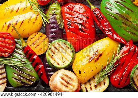 Grilled vegetables cooking on coal grill with spices and herbs. Top view flat lay