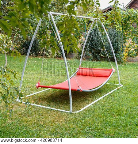 Hammock Swing In Metal Frame With Nobody On Green Lawn In Backyard Near House Cottage. Rest Relax Re