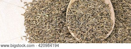 Cumin In A Wooden Spoon Isolated On A White Background. Banner. Caraway Seeds.