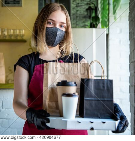Woman Waiter In Protective Medical Mask And Gloves Work With Takeaway Orders. Waiter Giving Takeout