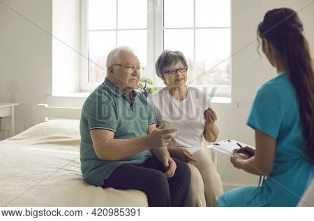 Worried Senior Couple Sitting On Bed And Talking To Nurse Or Family Practitioner