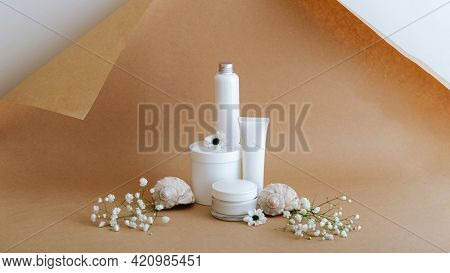 Set Natural Beauty Cosmetic Skincare Products With Flowers Sea Shells On Beige Brown Background. Whi