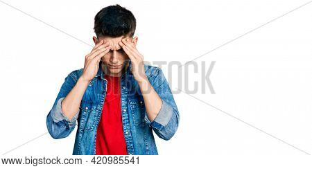 Young caucasian boy with ears dilation wearing casual denim jacket with hand on head for pain in head because stress. suffering migraine.