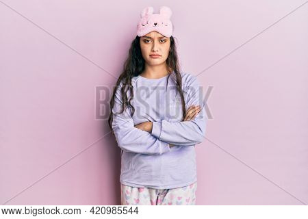 Beautiful middle eastern woman wearing sleep mask and pajama skeptic and nervous, disapproving expression on face with crossed arms. negative person.