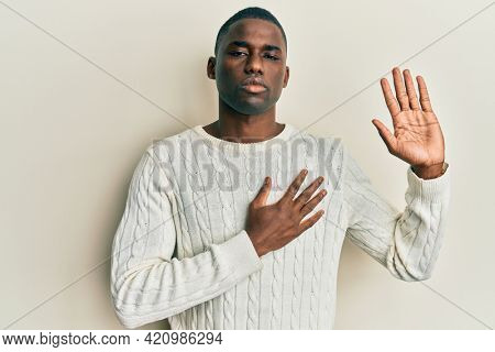 Young african american man wearing casual clothes swearing with hand on chest and open palm, making a loyalty promise oath