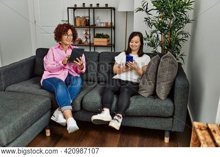 Mature mother and down syndrome daughter at home using smartphone and touchpad device