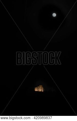 Illuminated Castle Habsburg Near Brugg With Super Moon At Night. Brugg, 27. April 2021. Vertical Sho