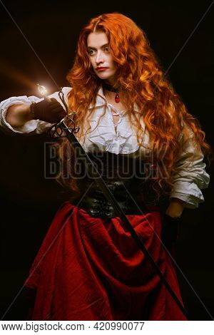 Portrait of a beautiful courageous woman with magnificent foxy hair holding her battle epee (rapier). Black background.