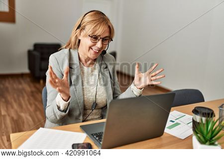 Middle age call center agent having video call using laptop at the office.