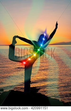 Silhouette of woman in yoga pose on beach sunset view, glowing seven all chakra. Kundalini energy. girl practicing meditation outdoors