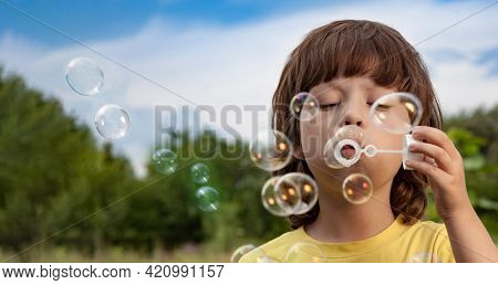 Happy Boy blowing a soap bubbles toy in garden sunny summer day.