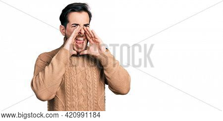 Young hispanic man wearing casual clothes shouting angry out loud with hands over mouth