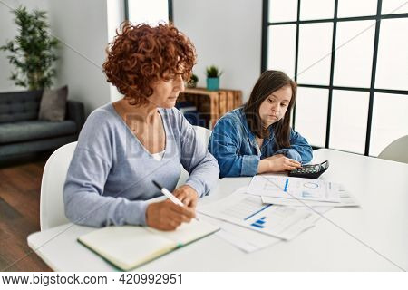 Mature mother and down syndrome daughter doing economy house together