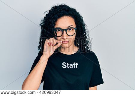 Young hispanic woman with curly hair wearing staff t shirt mouth and lips shut as zip with fingers. secret and silent, taboo talking