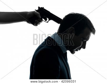 one caucasian businessman with gun pointing to his head in silhouette studio isolated on white background
