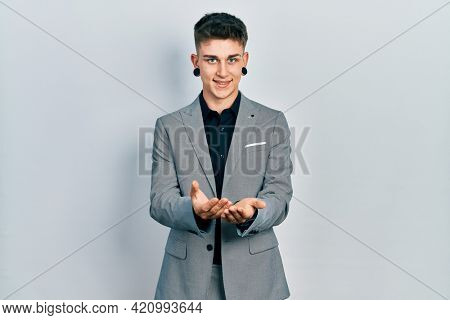 Young caucasian boy with ears dilation wearing business jacket smiling with hands palms together receiving or giving gesture. hold and protection