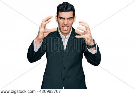 Handsome hispanic man wearing business clothes shouting frustrated with rage, hands trying to strangle, yelling mad