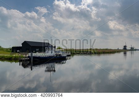 The Windmills And Canals Of Kinderdijk In South Holland With A Dock And Boat In The Foreground