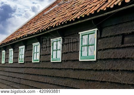 A Close Up Of The Tarred Wooden Siding Of A Traditional Dutch Farmhouse With Many Small Green Window