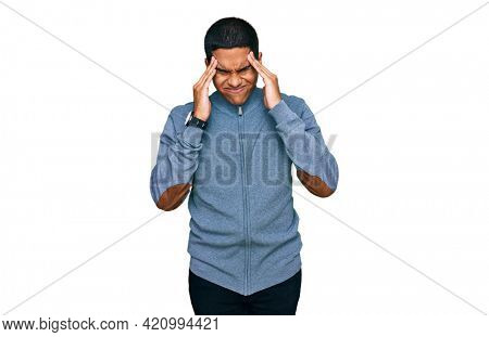 Young handsome hispanic man wearing casual sweatshirt with hand on head, headache because stress. suffering migraine.