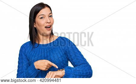 Young hispanic woman wearing casual clothes in hurry pointing to watch time, impatience, upset and angry for deadline delay