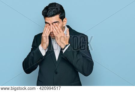 Handsome hispanic man wearing business clothes rubbing eyes for fatigue and headache, sleepy and tired expression. vision problem