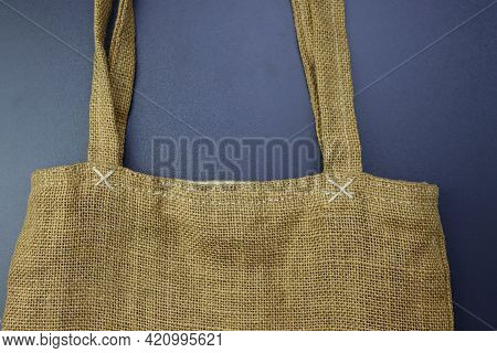 Part Of A Bag Made Of Hessian Fabric On A Gray Background. Women's Bag Made Of Burlap.
