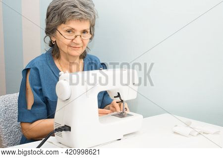 Portrait Of Smiling Elderly Woman With Glasses Using Sewing Machine At Home. Senior Woman Sewing, In