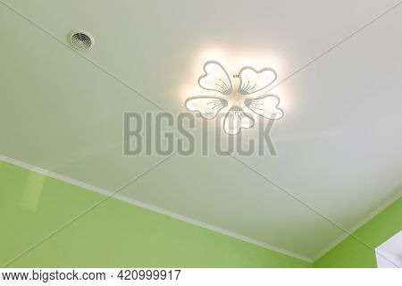 Ceiling With Led Chandelier And Air Vent. Decorative Led Chandelier In The Form Of A Flower Under Th