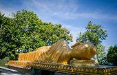 A big golden statue of Buddha sleeping, poster