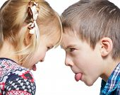 Sister and brother stick out tongues to each other poster