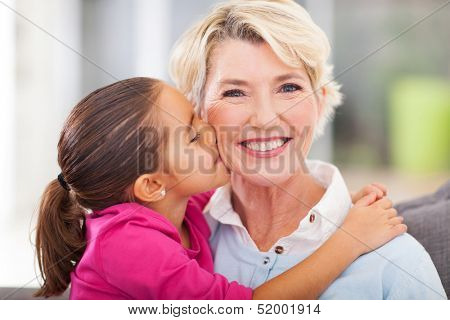 loving cute granddaughter kissing her grandmother at home