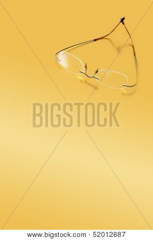 Rimless Glasses On A Golden Surface