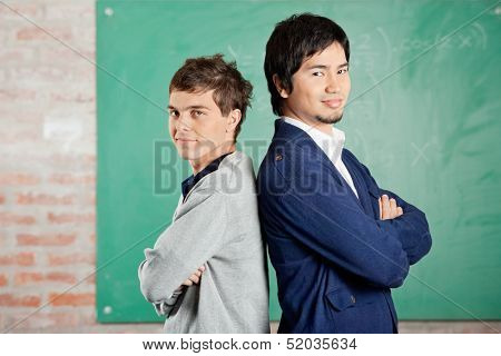 Side view portrait of confident young students standing arms crossed against greenboard in classroom