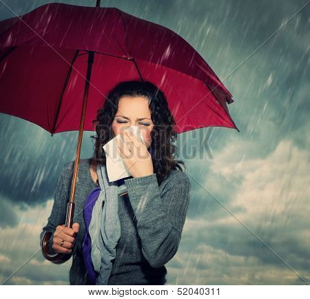 Sneezing Woman with Umbrella over Autumn Rain Background. Sick Woman outdoors. Flu. Girl Caught Cold. Sneezing into Tissue. Headache. Virus. Bad Weather