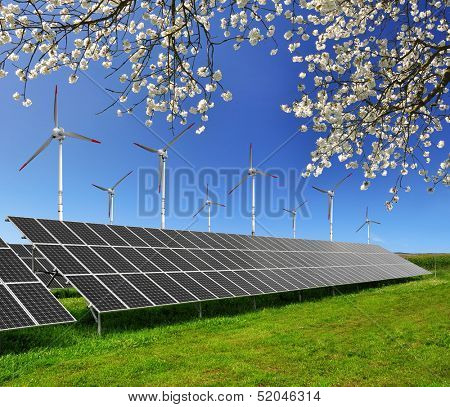 Solar energy panels and wind turbines against blue sky