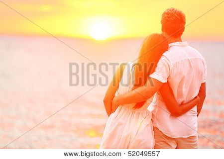 Honeymoon couple romantic in love at beach sunset. Newlywed happy young couple embracing enjoying ocean sunset during travel holidays vacation getaway. Interracial couple, Asian woman, Caucasian man.
