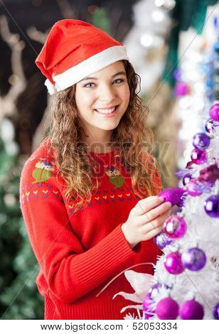Portrait of happy female owner decorating Christmas tree at store