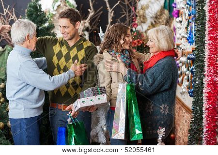 Happy family with shopping bags and presents embracing each other in Christmas store
