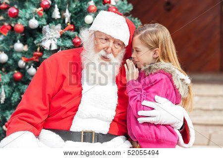 Girl telling wish in Santa Claus's ear against Christmas tree