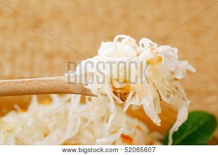 Sour cabbage - sauerkraut - on wooden spoon