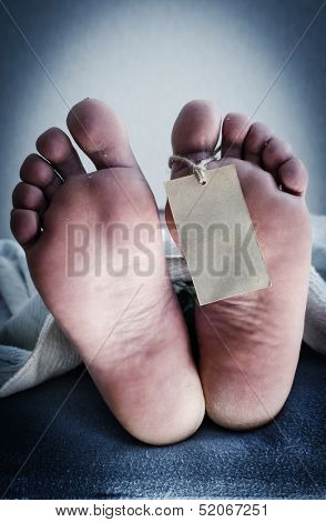 Two feet of a dead body, with an identification tag. Blue toned.